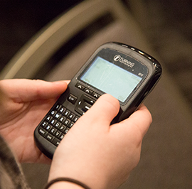 A closeup of a handheld electronic voting device, held by two hands