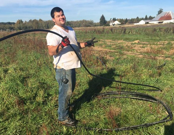 A young man standing out in a field, holding irrigation tubing