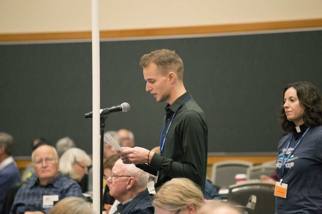 A young man stands at a microphone, reading from a paper in a room with people sitting and a female priest standing behind him