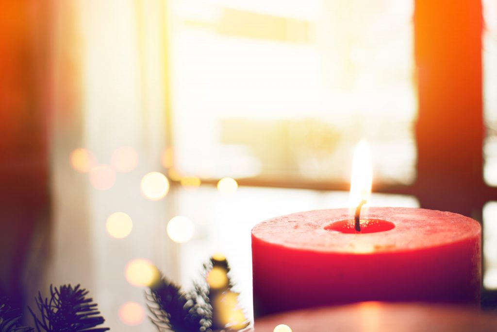 An Advent candle in the foreground, with a sunlit window and Christmas lights in the background.