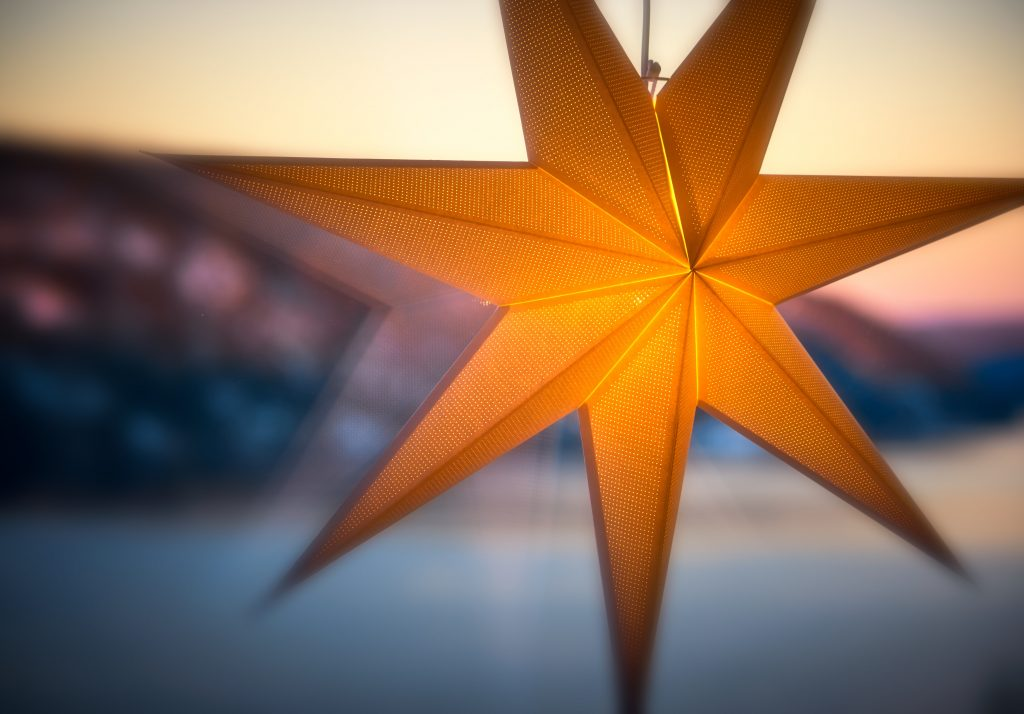 A brown paper star, hanging and illuminated by a light